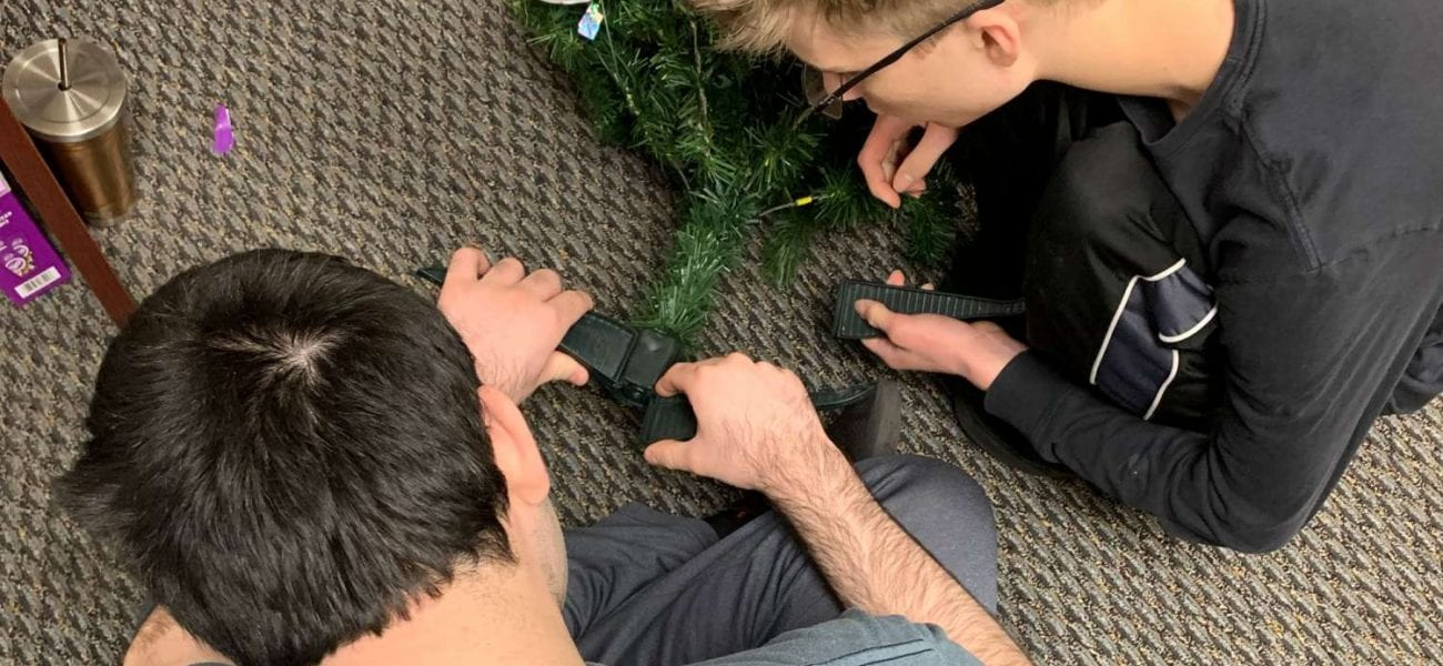 Two students building a small christmas tree