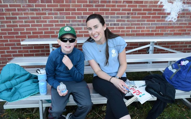 a student sitting outside on bleachers with a teacher